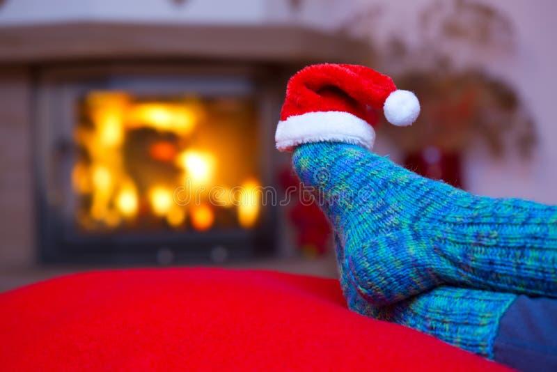Voeten in wollen blauwe sokken en Kerstmanhoed royalty-vrije stock afbeeldingen