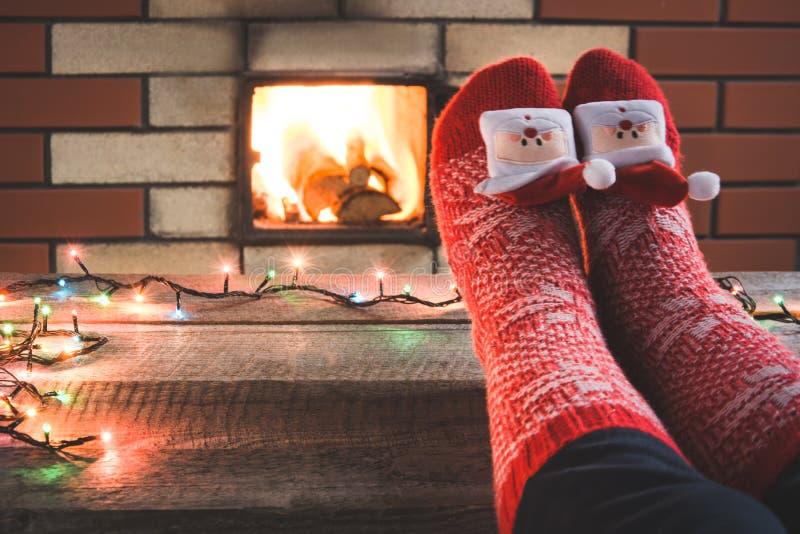 Voeten in wollen rode Kerstmissokken door de open haard Sluit omhoog op voeten Tafelblad voor vertoning uw Kerstmisproduct stock afbeeldingen