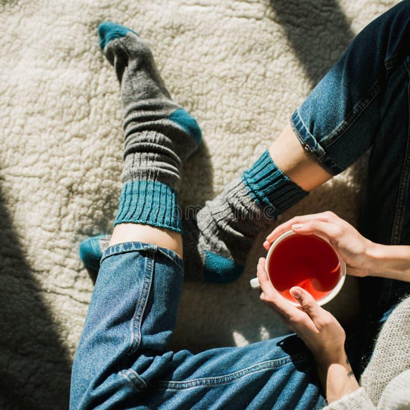 Voeten in wollen sokken De vrouw ontspant met een kop van hete drank en het opwarmen van haar voeten in wollen sokken Sluit omhoo royalty-vrije stock afbeelding