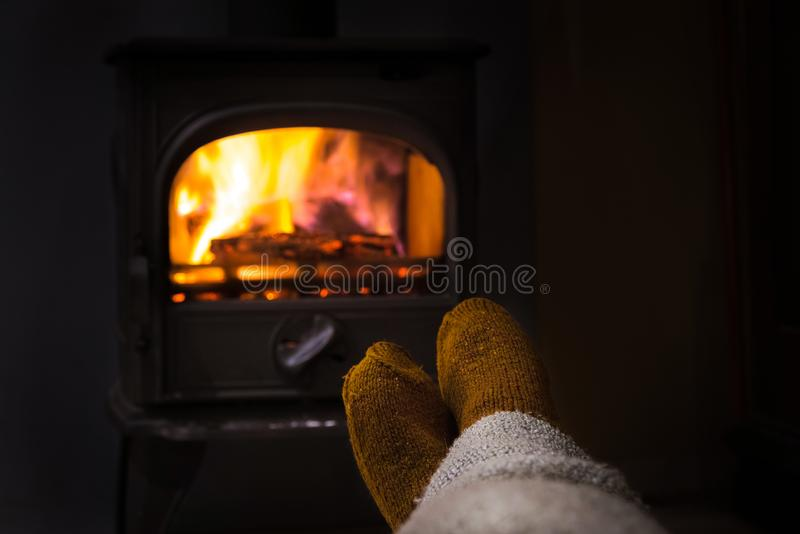 Voeten in wollen sokken door de Kerstmisopen haard Vrouw of man r stock afbeelding
