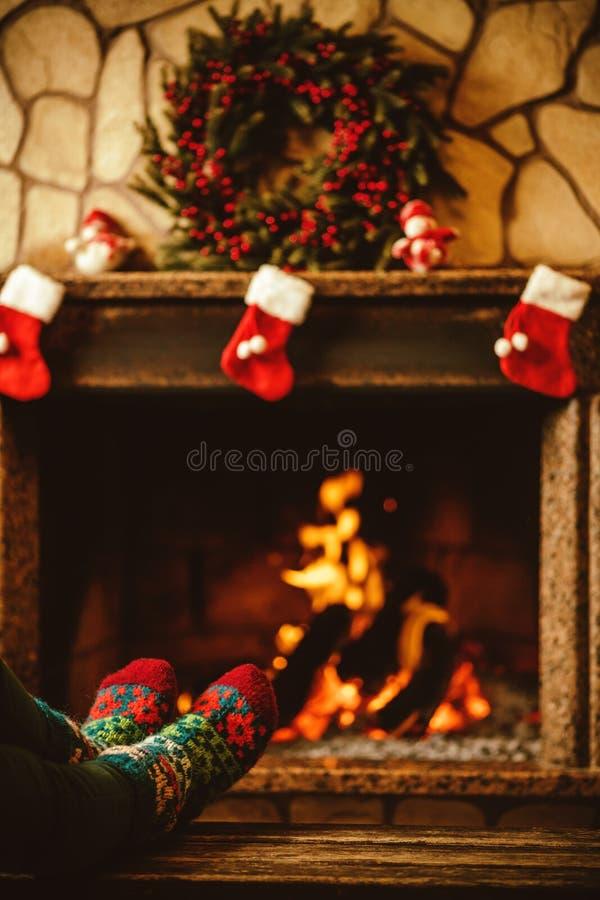 Voeten in wollen sokken door de open haard De vrouw ontspant door warm FI stock afbeelding