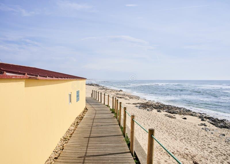Voetenwerk tussen geel huis en het strand stock afbeeldingen