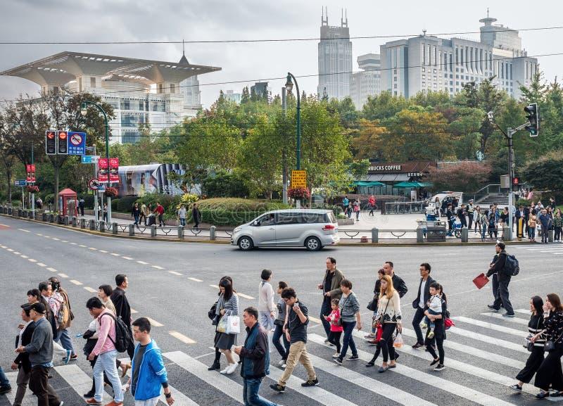 Voetgangers bij de gestreepte kruising langs de Middenweg van Xizang, Shanghai, China royalty-vrije stock afbeeldingen
