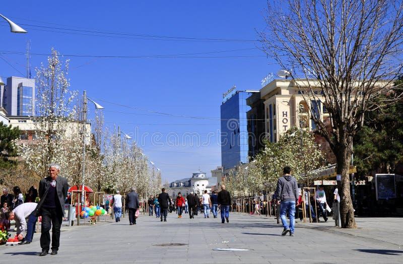 Voetgangers die langs Boulevard Nene Tereza in Pristina lopen stock foto