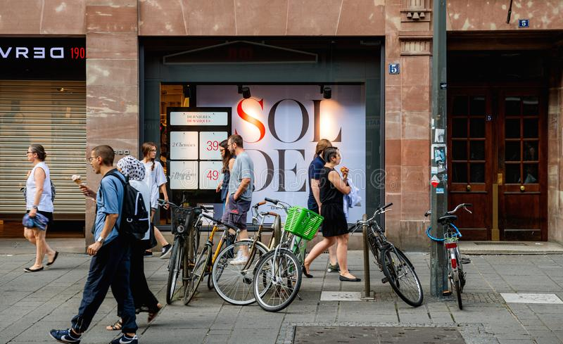Voetgangers die voor Soldes-Verkoopteken lopen stock fotografie