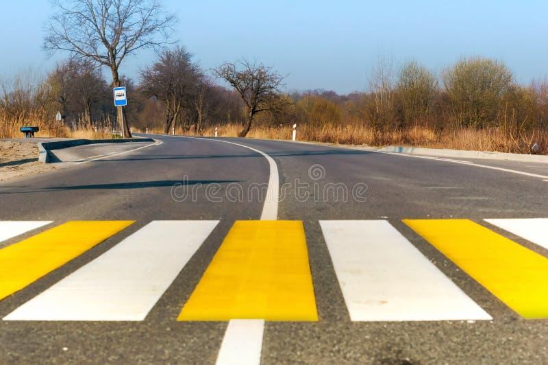 Voetgangersoversteekplaats buiten de stad, witte gele noteringen op de weg royalty-vrije stock foto