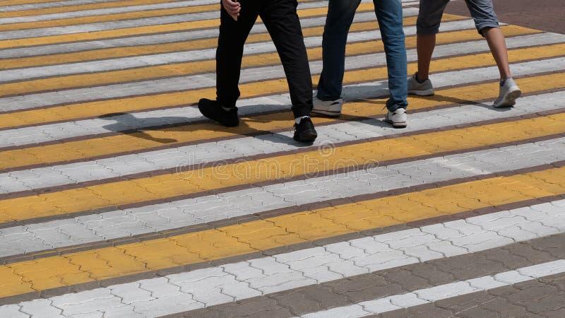Voetgangersoversteekplaats op de steenweg Witte en gele strepen waarop drie mensen in tennisschoenen overgaan Benen van mensen in royalty-vrije stock afbeelding