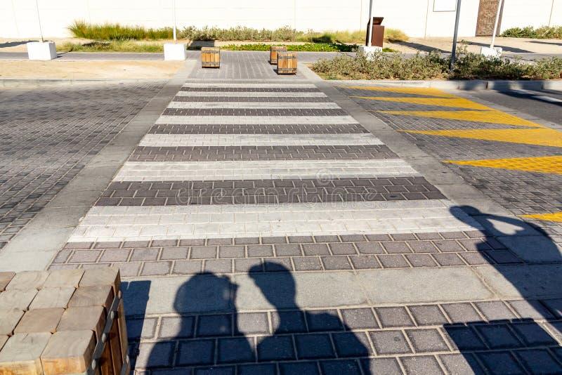 Voetgangerssilhouetten die de weg dichtbij het zebrapad voorbereidingen treffen te kruisen royalty-vrije stock afbeeldingen
