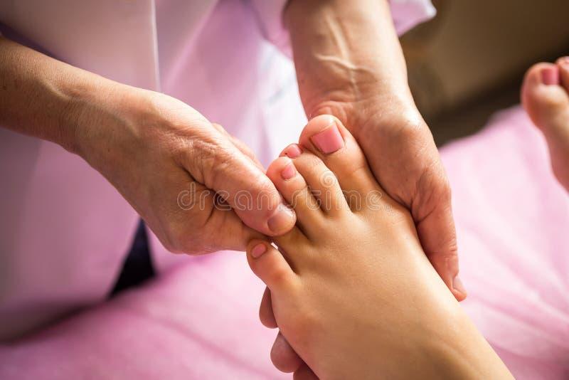 Voetmassage in kuuroordsalon, close-up die, Jonge vrouw voetenmassa hebben royalty-vrije stock afbeeldingen