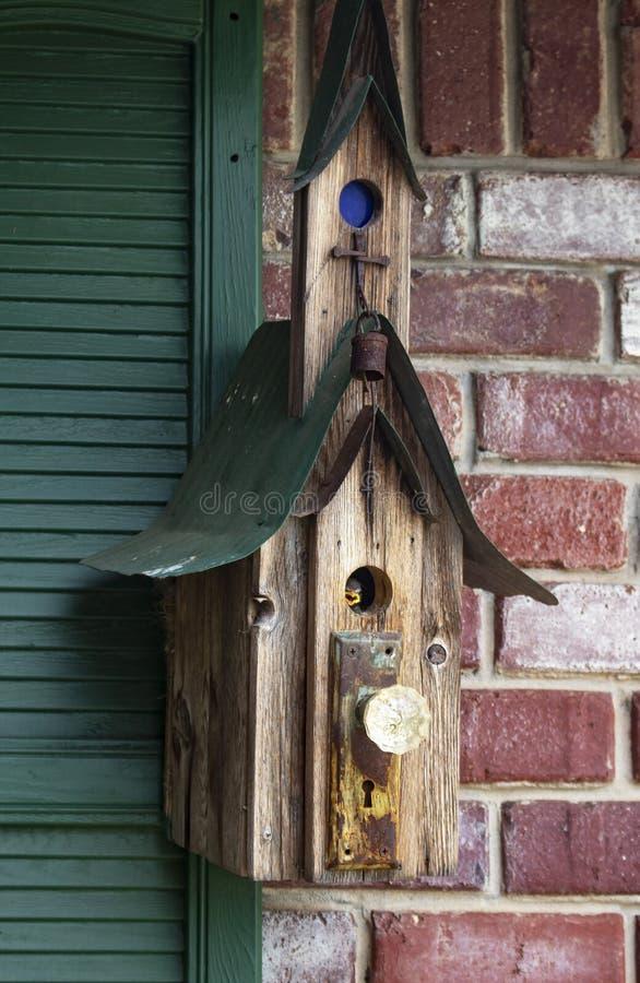 Vogelbabywartemutter innerhalb der runden Tür des rustikalen Vogelhauses hing an der Backsteinmauer und an den grünen Fensterläde stockbild