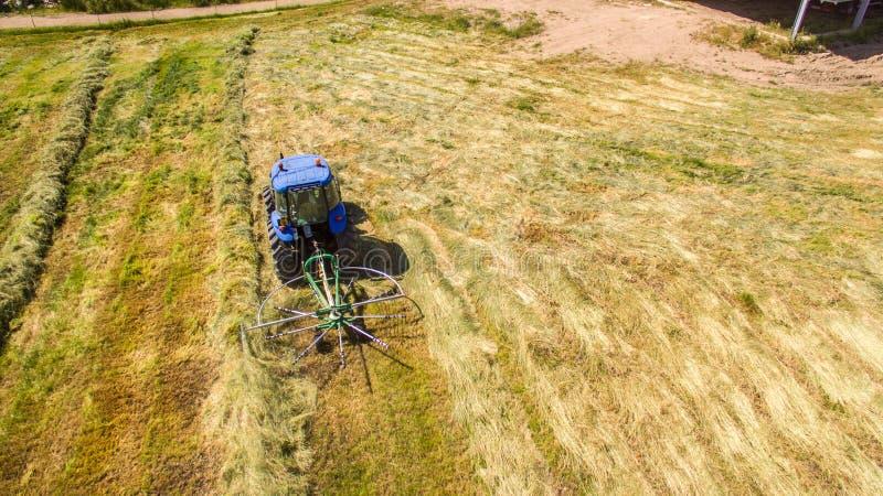 Vogeloog van de tractor die van de Hooihark het hooi draaien stock foto