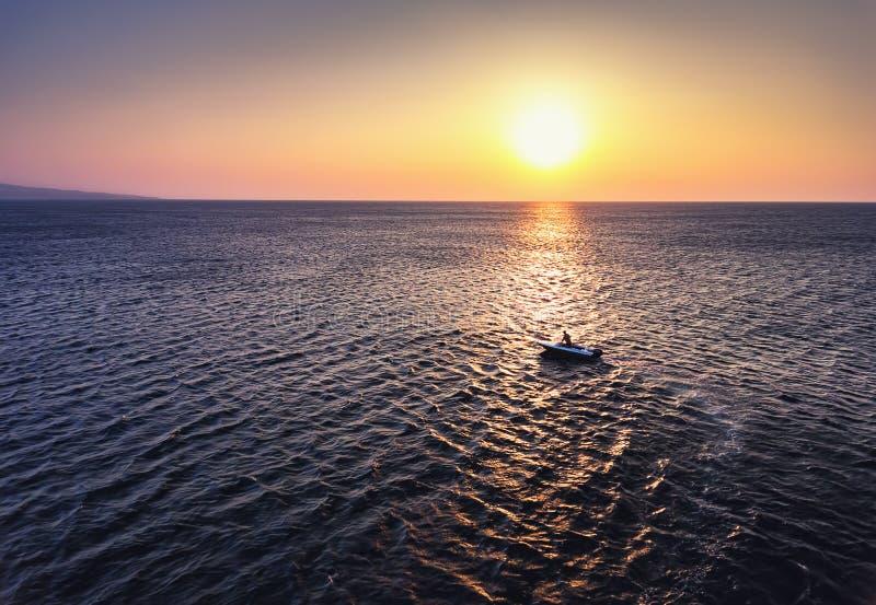 Vogelperspektive über Fischerboot auf dem Wasser und dem schönen Sonnenaufgang stockbilder