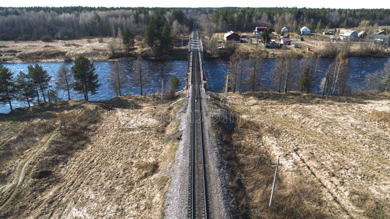Vogelperspektive auf der Bahnbrücke über dem Fluss im ländlichen Platz im Frühjahr stockfotografie