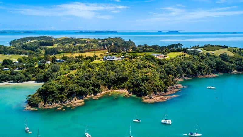 Vogelperspektive auf einer umgebenden felsigen Halbinsel des schönen Hafens mit Wohnhäusern Waiheke-Insel, Auckland, Neuseeland stockfotografie