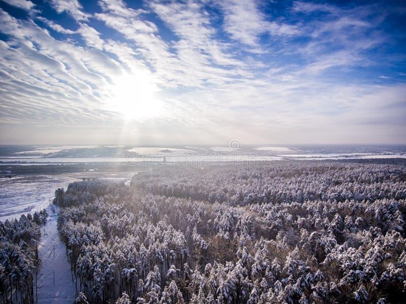 Vogelperspektive auf Schneewinterwald und Feld nahe Straße Gefrorener Fluss auf Hintergrund Wolken mit Sonne im blauen Himmel stockfotografie