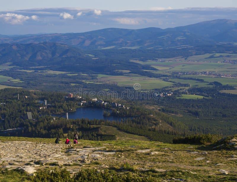 Vogelperspektive auf Strbske Pleso Dorf und blauem Gebirgssee von chata Hülse soliskom mit Wald, Hügeln und Gruppe entspannendem  stockbild