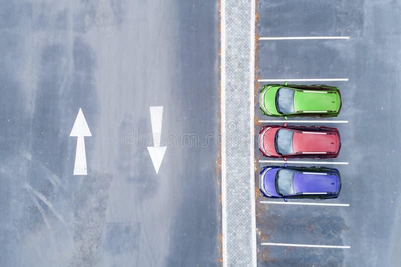 Vogelperspektive-Brummenspitze unten des Parkplatzes mit Autos und des Pfeilzeichens auf Straße lizenzfreies stockbild