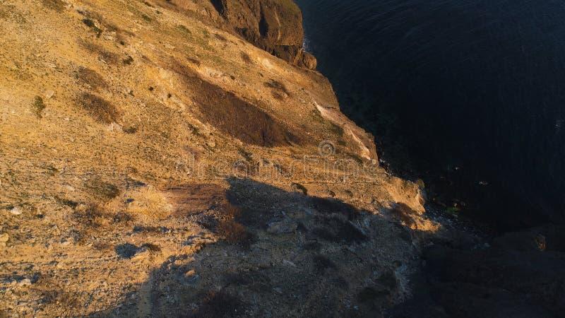 Vogelperspektive der felsigen ruhigen Ozeanküste bei dem Sonnenuntergang schu? Schöne Ansicht vom Klippenrand auf der Ozeanoberfl stockbild