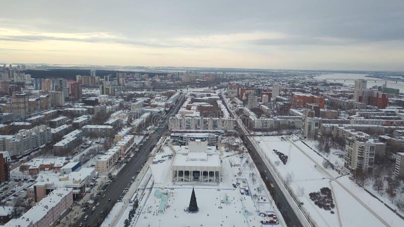 Vogelperspektive der großen Gasse umfasst mit Schnee und Quadrat mit Weihnachtsbaum in der Mitte der Stadt gegen grauen Abend stockfoto