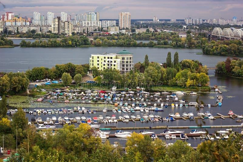 Vogelperspektive der Kiew-Stadt von einer Beobachtungsstelle über dem Dnieper-Fluss mit Eisenbahnbrücke yachts am Liegeplatz und  stockbild