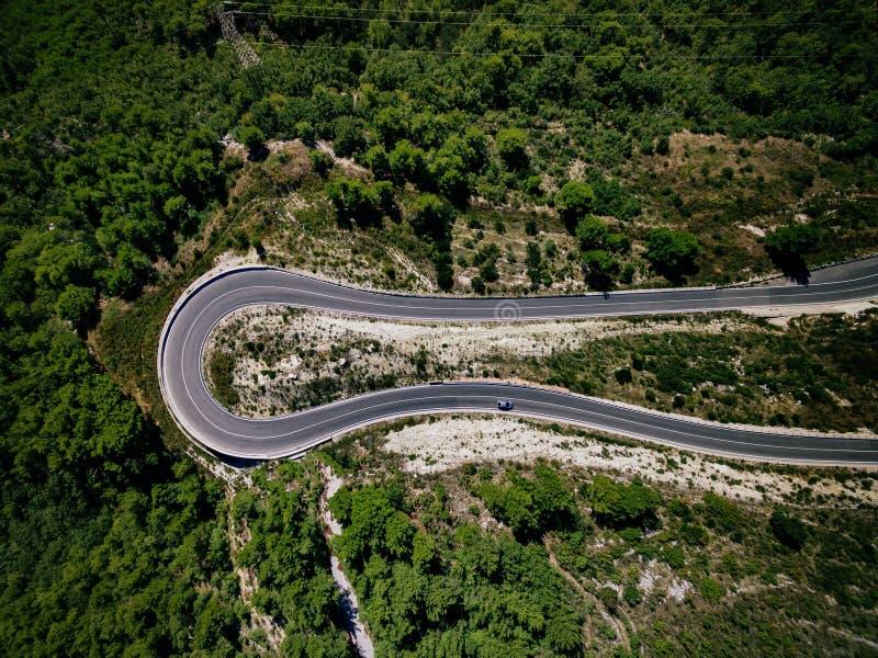 Vogelperspektive der Kurvenstraße mit einem Auto auf dem Berg mit grünem Wald in Kroatien lizenzfreies stockbild
