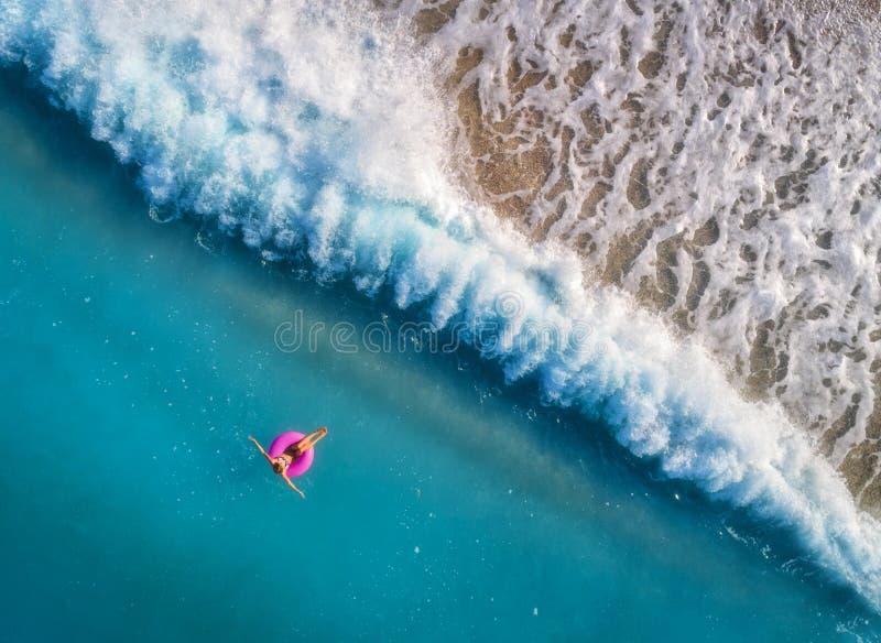 Vogelperspektive der Schwimmens der jungen Frau auf dem rosa Schwimmenring lizenzfreie stockbilder