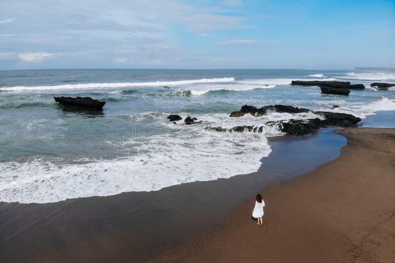 Vogelperspektive der unerkennbaren Frau im weißen Kleid gehend nahe Ozean und Sommertag auf Strand genießen Ferien in Bali lizenzfreies stockfoto