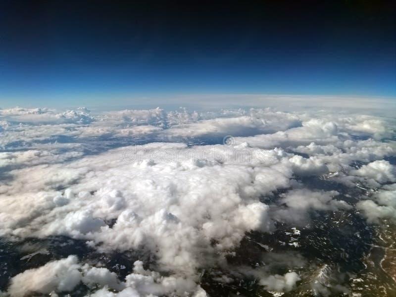Vogelperspektive der Wolke umfasste Berglandschaft mit dem Schnee, der auf grünen Hügeln mit bewölktem Himmel mit der Erdkrümmung stockfotos