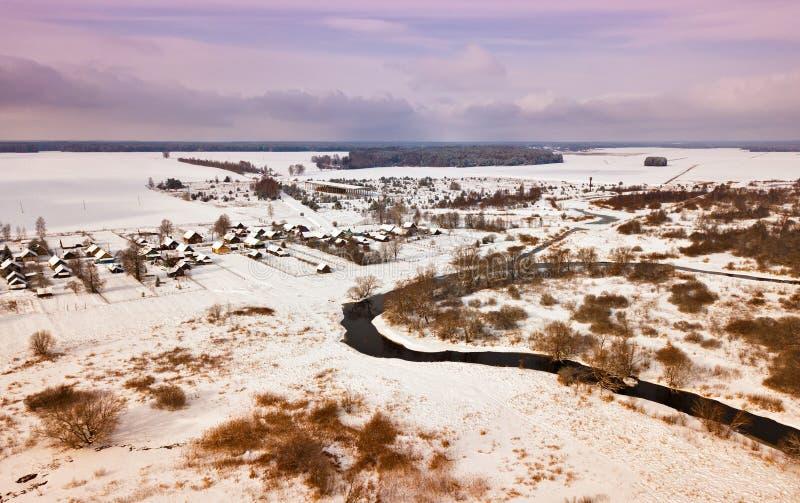 Vogelperspektive des Dorfs, des Flusses, der Wiese und des Waldes bedeckt durch Schnee lizenzfreie stockfotografie