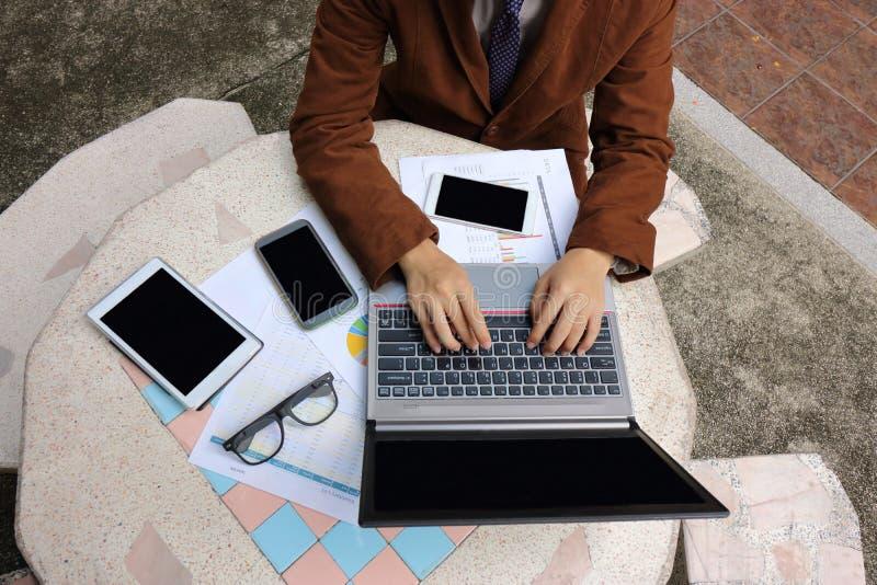 Vogelperspektive des jungen Geschäftsmannes, der einen Laptop mit leerem Bildschirm gegen Tablette, Telefon und Diagramme auf Mar stockfotografie
