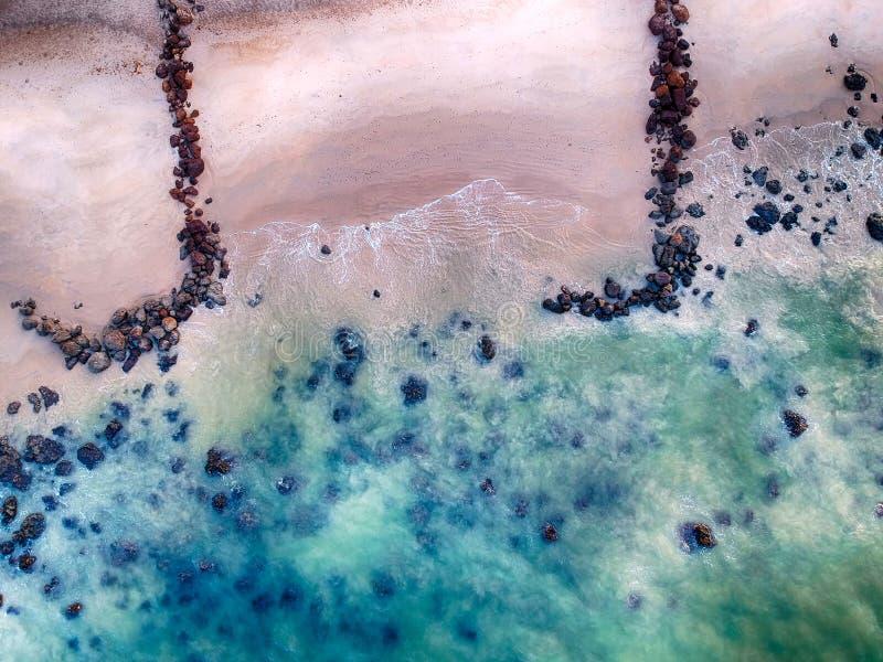 Vogelperspektive des sandigen Strandes mit Wellen, klarem Ozeanwasser und großen schwarzen Steinen Es ist tropisches Paradies in  stockfoto