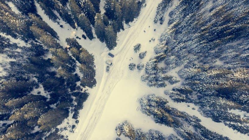 Vogelperspektive des Schnees bedeckte Straße durch einen Wald stockbilder