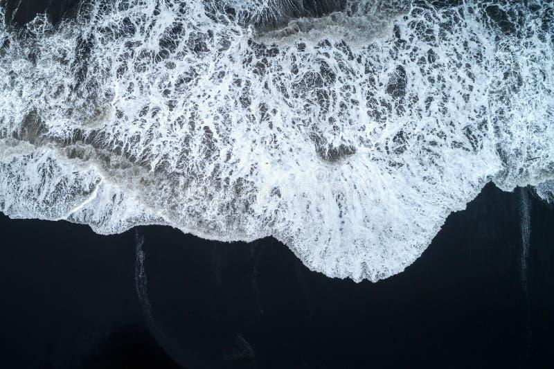 Vogelperspektive des schwarzen Sandstrandes und Meereswogen in Island stockbilder