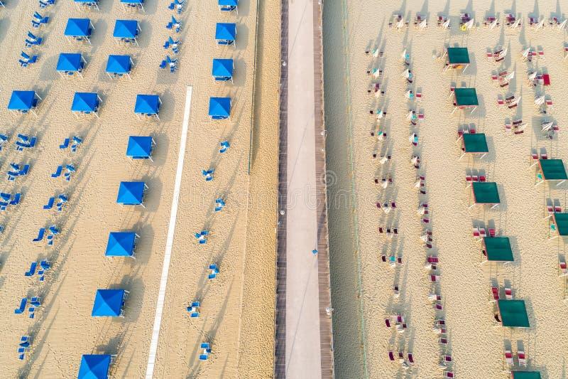 Vogelperspektive des Strandes mit weißem Sand, Regenschirmen und Stühlen stockbilder