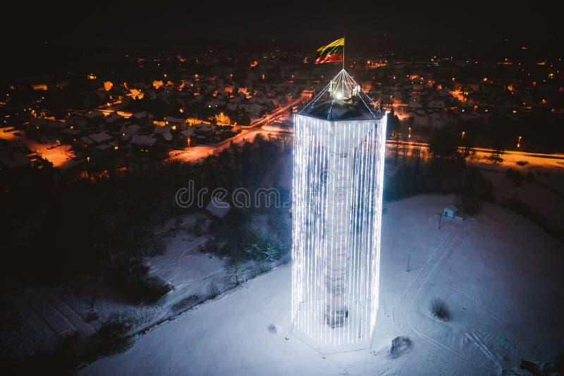 Vogelperspektive des Wasserturms verziert mit Weihnachtslichtern und litauischer Flagge in Pasvalys-Stadt nachts lizenzfreie stockfotos
