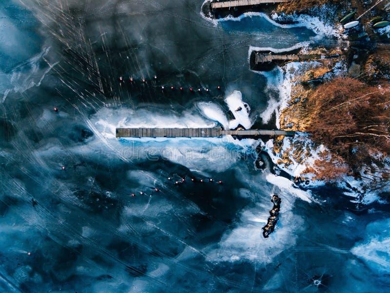 Vogelperspektive des Winter gefrorenen Sees mit hölzernen Piers nahm mit einem Brummen in Finnland gefangen stockbild
