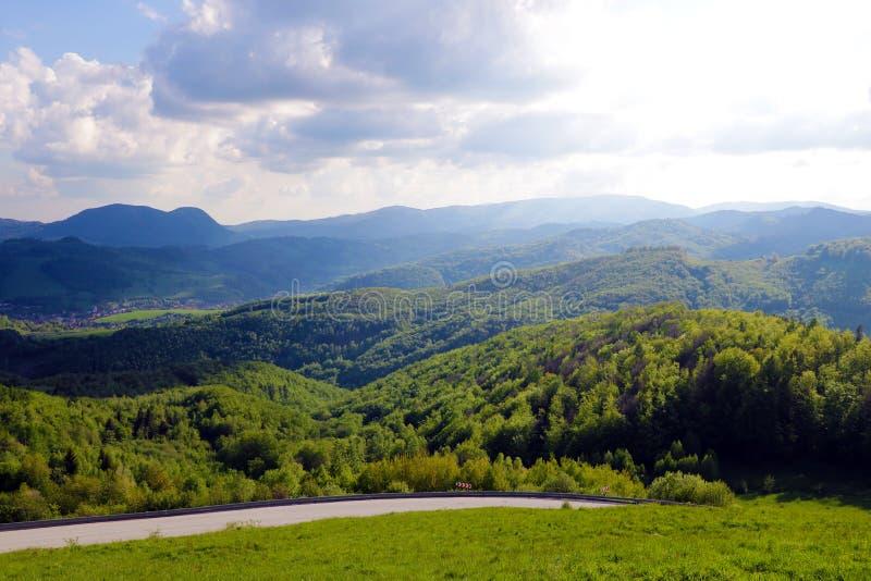 Vogelperspektive einer Straße, die Wälder und Dörfer in Slowakei mit Tatra-Bergen im Hintergrund durchläuft lizenzfreie stockfotografie