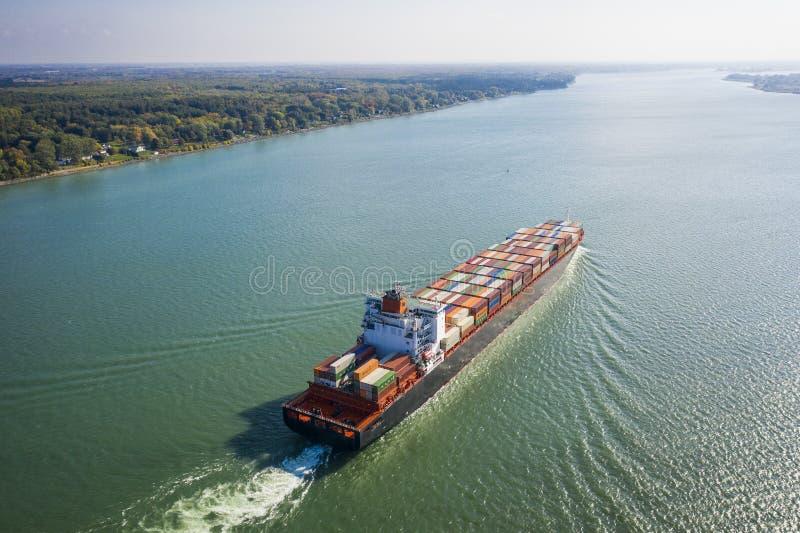 Vogelperspektive eines Containerschiffs, das gegen den Strom in das St. Lawrence River nahe dem Hafen von Montreal in Kanada geht stockfotos