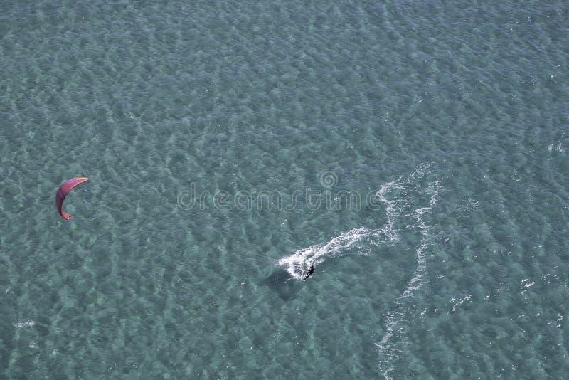 Vogelperspektive eines Drachensurfers, der auf sardinischem Wasser des Türkises zur Schau trägt lizenzfreie stockbilder
