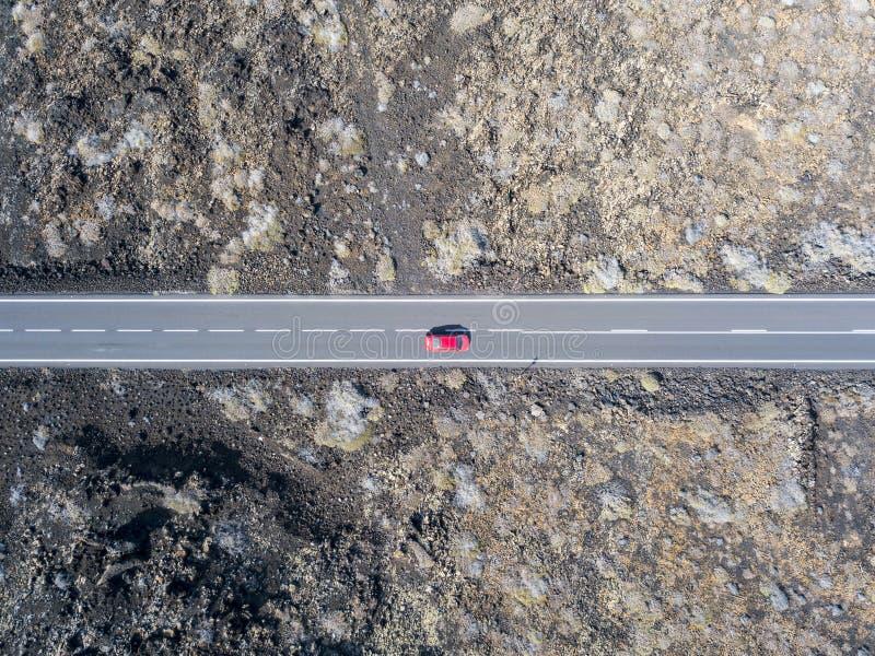Vogelperspektive eines roten Autos auf einer Straße, die durch Lavafelder von Lanzarote läuft, Kanarische Inseln, Spanien stockfoto