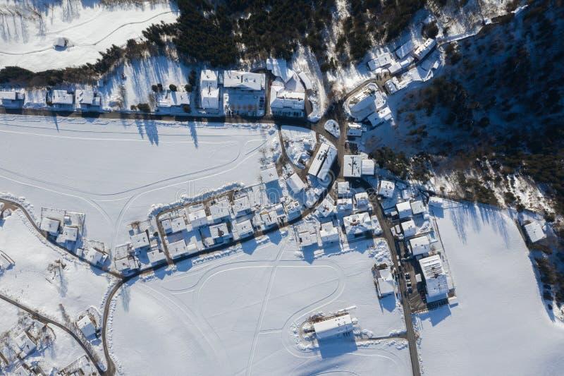 Vogelperspektive traditionellen österreichischen Dorfs Itter bedeckt durch Schnee am Winter-Morgen stockbild