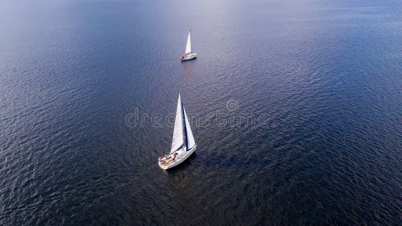 Vogelperspektive vom Brummen der Yachten mit weißen Segeln in Meer stockbild