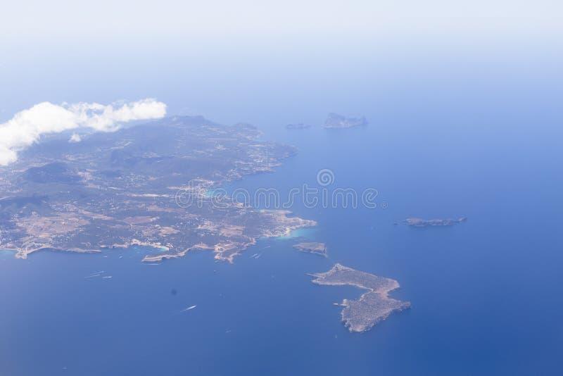 Vogelperspektive vom Flugzeug von Ibiza-Insel mit blauem schönem Wasser Wolken Feiertage und Sommerkonzept stockbild