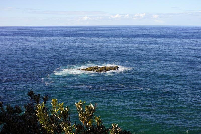Vogelperspektive von blauem Meer mit kleiner Felseninsel stockbild