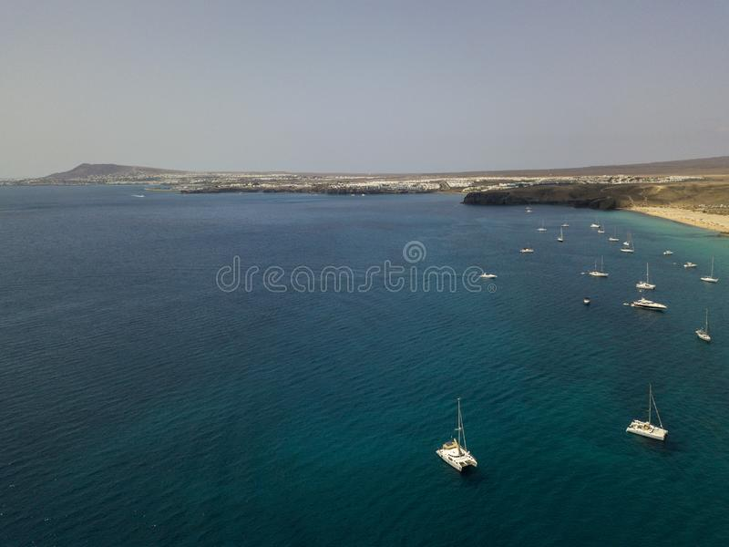 Vogelperspektive von den festgemachten Booten, die auf ein transparentes Meer schwimmen Zitronengelbe Küste, Lanzarote spanien lizenzfreie stockbilder