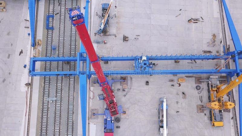 Vogelperspektive von den roten und gelben anhebenden Kränen installiert nahe der Eisenbahn in das Industriegebiet clip Bau und stockbild