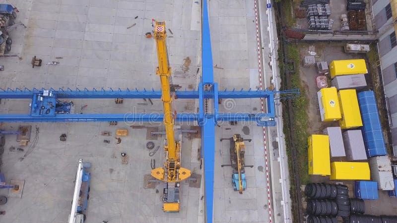 Vogelperspektive von den roten und gelben Baukränen installiert nahe gelben Frachtbehältern und von Eisenbahn in stockfotos