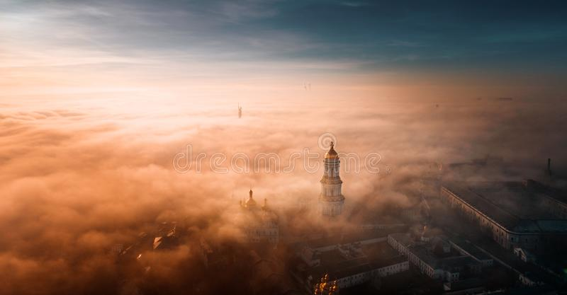 Vogelperspektive von Kiew Pechersk Lavra an der Dämmerung und von Stadt bedeckt mit starkem Nebel im Hintergrund stockfotografie