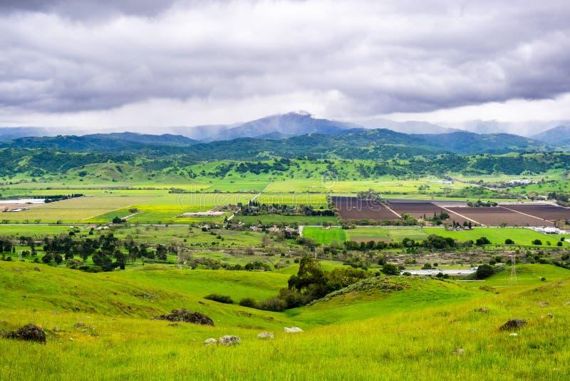 Vogelperspektive von landwirtschaftlichen Feldern und von grünen Hügeln am bewölkten Frühlingstag; Santa Cruz-Berge im Hintergrun lizenzfreie stockfotografie