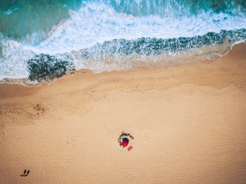 Vogelperspektive von Meereswogen und von Sandstrand mit dem Touristengehen - Sommerferien-Ferienkonzept mit Leuten - blau und gel lizenzfreies stockbild